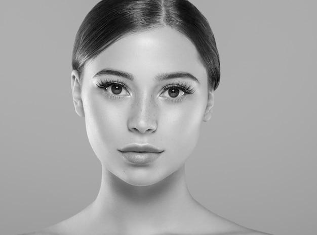 Глаза ресницы лицо женщины крупным планом естественный составляют здоровую кожу. студийный снимок. монохромный. серый. черное и белое.