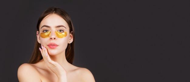 눈 마스크 화장품 패치 여자 얼굴 근접 촬영입니다. 황금 눈 패치를 적용하는 여자. 초상화 소녀를 닫습니다. 완벽한 피부의 효과를 보여주는 눈 패치를 가진 미인의 초상화.