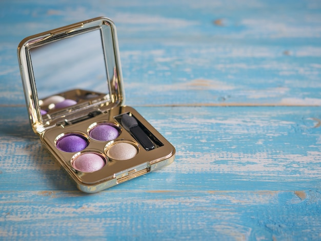 Eyeshadow in a golden box with mirror on blue wooden table.