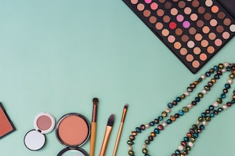 Eyeshadow palette; beads necklace; blusher with makeup brushes on pastel backdrop
