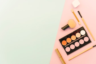 Eyeshadow palette; lipstick; brush and cosmetics products on dual background