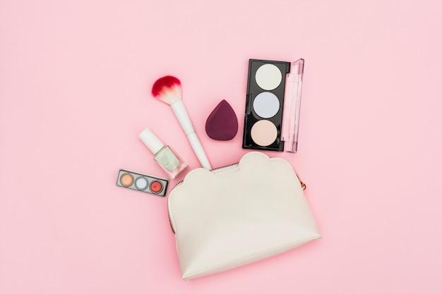 아이 섀도우 팔레트; 매니큐어 병; 블렌더; 분홍색 배경에 메이크업 브러시와 메이크업 가방