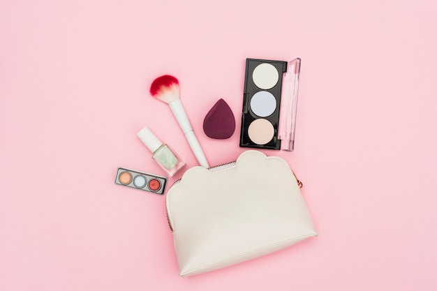 Eyeshadow palette; nail polish bottle; blender; makeup brush and makeup bag on pink background