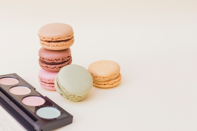 Eyeshadow palette and stack of macaroons over beige background