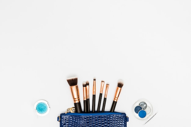 Eyeshadow palette with makeup brushes from blue bag on white background