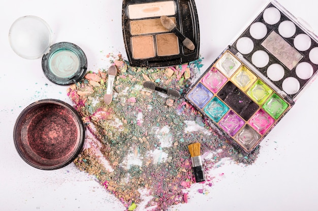 Eyeshadow powders with various brushes on white background