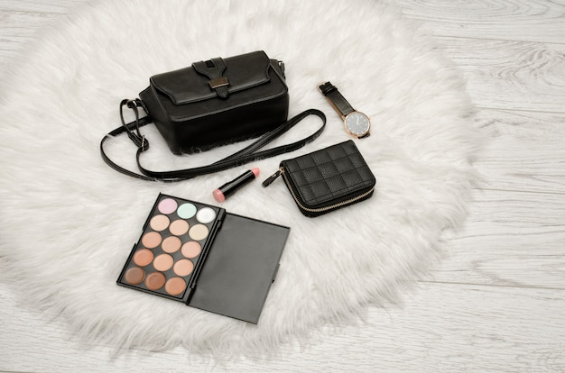 아이 섀도우, 지갑, 립스틱, 시계 및 백색 모피에 검은 핸드백. 패션 컨셉