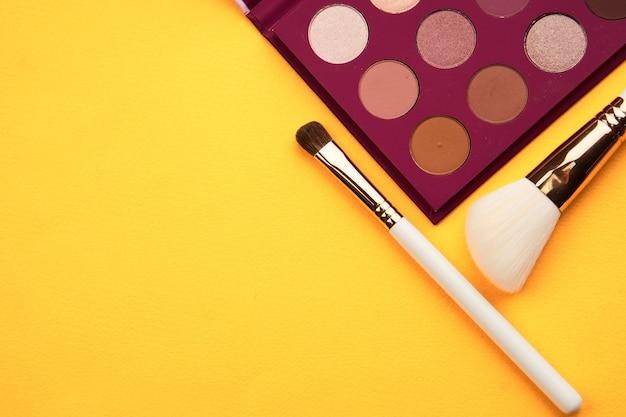 Тени для век и кисти для макияжа на желтом фоне вид сверху профессиональная косметика