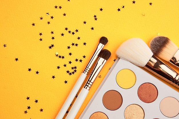 Eyeshadows and makeup brushes on a yellow background top view professional cosmetics.