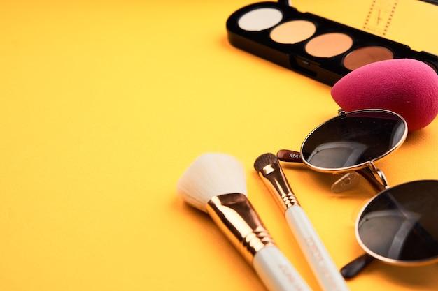 Тени для век на желтом столе, профессиональные косметические кисти для макияжа, мягкие губки, модные очки.