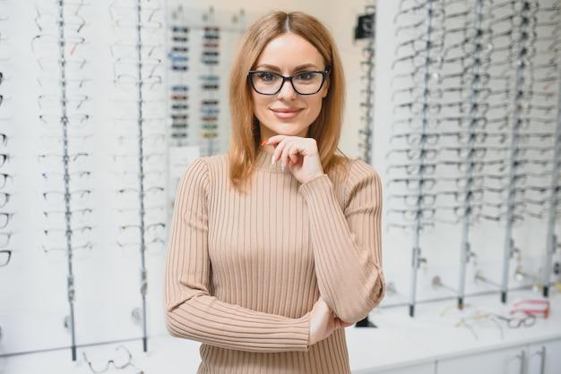 Концепция зрения и зрения - молодая деловая женщина, выбирая очки в магазине оптики