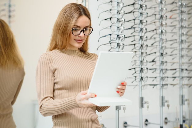 Eyesight and vision concept - young business woman choosing glasses at optics store