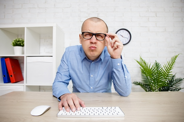 Eyevision problems - man using computer, holding glasses on his face and peering into the distance trying to see something