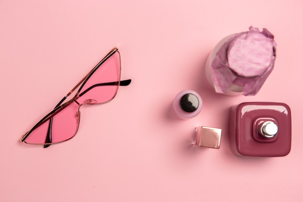 Eyewear, cosmetics, parfume. monochrome stylish and trendy composition in pink color on studio wall. top view, flat lay. pure beauty of usual things around. copyspace for ad. fashion.