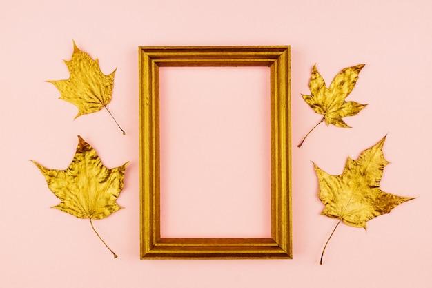 F 황금 페인트 단풍 잎과 분홍색 배경에 나무 포토 프레임. 유행 개념. 미니멀리즘 스타일의 플레임