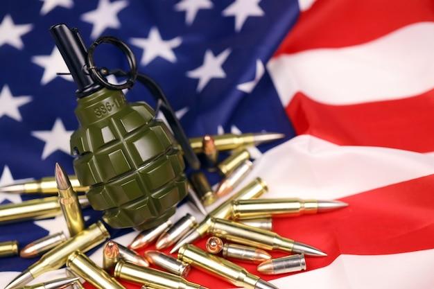 F1 수류탄과 미국 국기에 많은 노란색 총알과 카트리지. 미국 영토 또는 특수 작전에 대한 총기 밀매의 개념