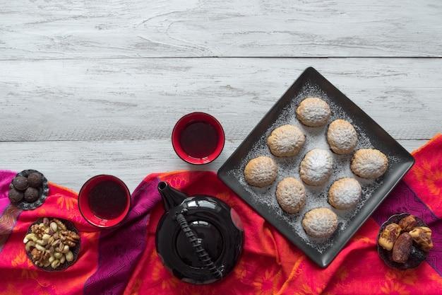 手作りのラマダンのお菓子には、背景にお茶が添えられています。エジプトのクッキー「カフエルイード」-エルフィットイスラムf宴背景のクッキー