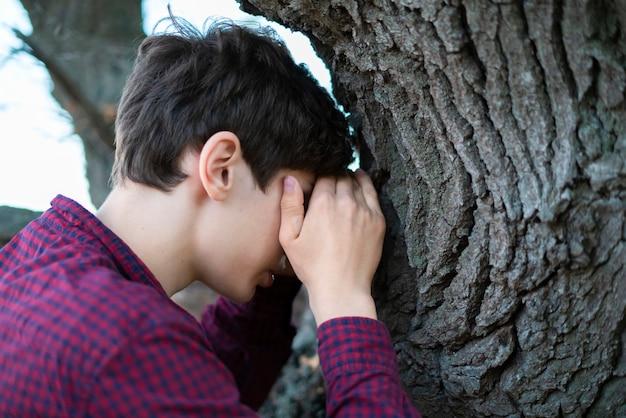 若い男は、目を閉じてfかくれんぼをプレイをカウントします。