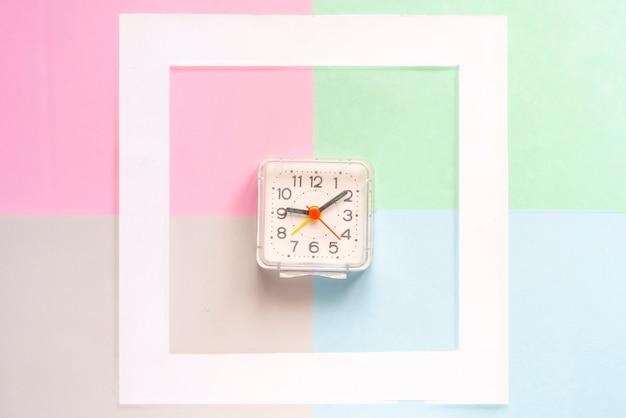 色表面fに分離された白い空のフレームでヴィンテージ時計とシンプルなコンセプトのトップビュー