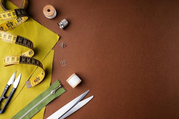 Ткань и швейные инструменты для рукоделия на коричневом фоне, плоская квартира, вид сверху, копия пространства.