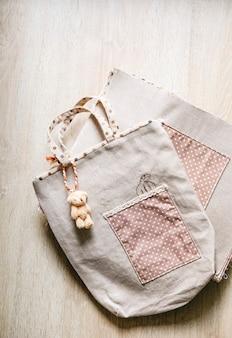 Тканевая сумка висит кукла медведь на деревянном фоне