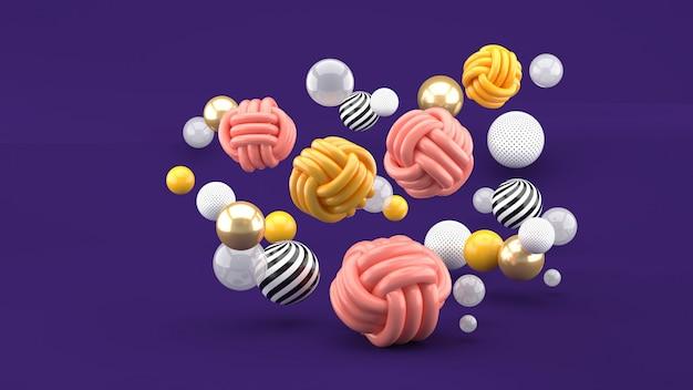 Fabric balls among colorful balls on purple space