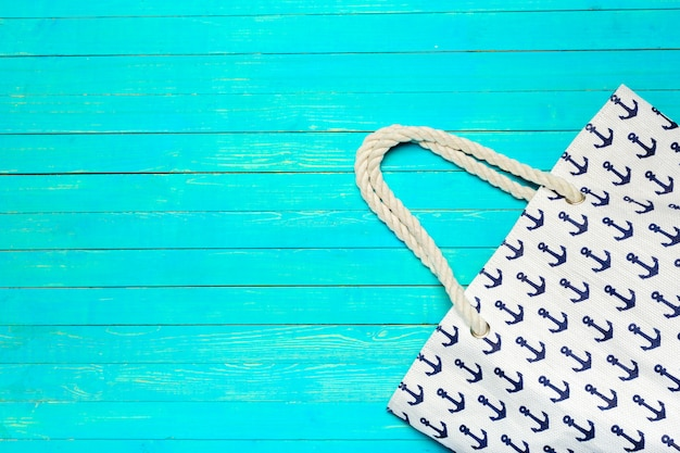 Fabric colored beach bag on bright blue wood