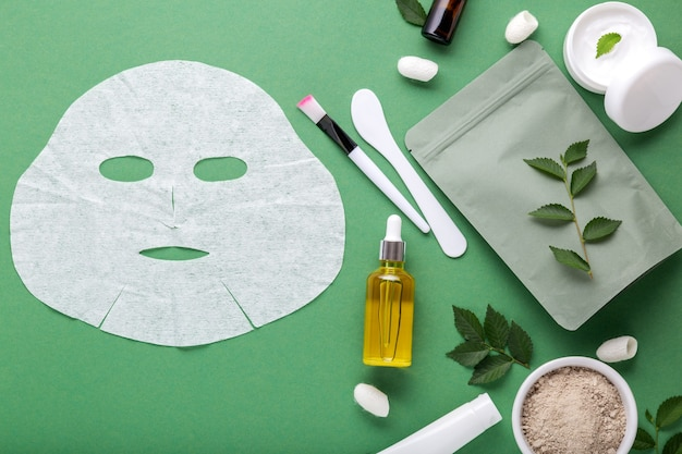 Fabric cosmetic face mask with set of cosmetics clay mask serum oil spatula brush, moisturizing cream in jar. beauty spa treatments for facial skin care, cosmetology on green surface with leaves.