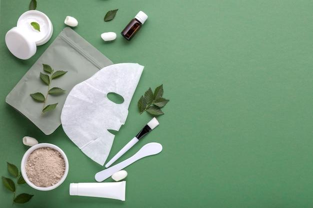 化粧品の布製マスクへらとブラシのセット、チューブ、ジャーの保湿クリームを備えたファブリック化粧品フェイスマスク。フェイシャルスキンケア、緑の背景の美容のための美容スパトリートメントコピースペース。