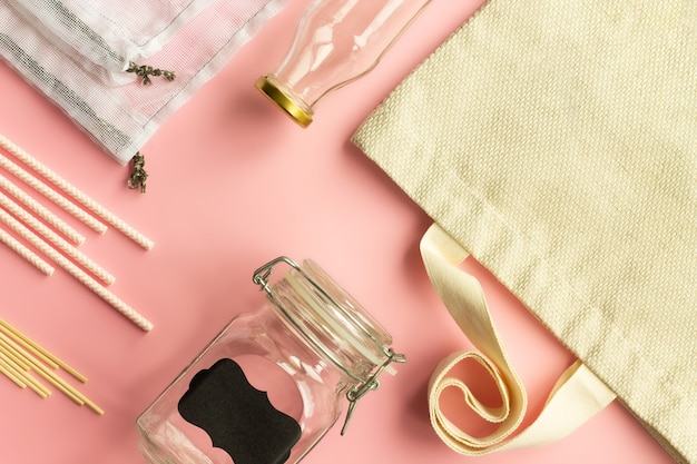 Сумки для покупок из хлопка ткани, стеклянные бутылки, бумажные соломинки и деревянные палочки на розовом фоне. вид сверху. скопируйте пространство.