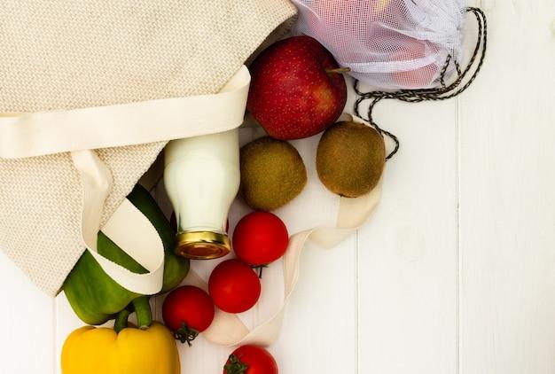 Хозяйственные сумки хлопка ткани с овощами и фруктами и стеклянной бутылкой молока на белой деревянной предпосылке. вид сверху. скопируйте пространство. безотходная и экологически чистая концепция.