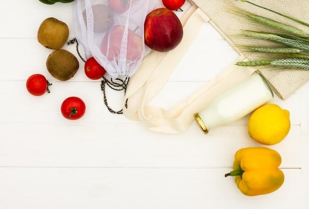 흰색 나무 배경에 야채와 과일, 우유 한 병이 든 패브릭 면 쇼핑백. 평면도. 공간을 복사합니다. 제로 폐기물 및 친환경 개념.