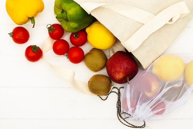 Хозяйственные сумки хлопка ткани с овощами и фруктами на белой деревянной предпосылке. вид сверху. скопируйте пространство. безотходная и экологически чистая концепция.