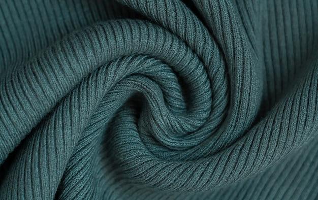 生地の濃い緑色の背景。暖かいニットセーターの質感