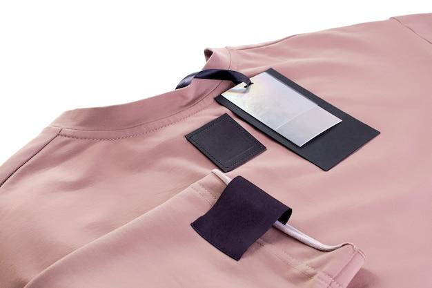 ベージュの服の袖のエコ レザー タグと紙ラベルのブランド ロゴ用の生地の空の黒いパッチ