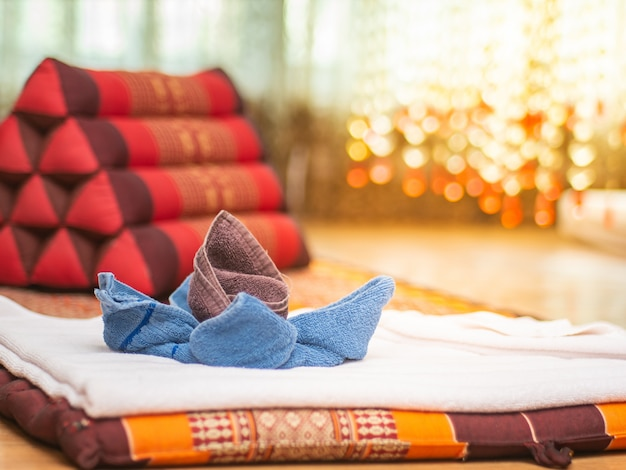 Fabric folded in flower shape with triangular pillow in vintage massage room.