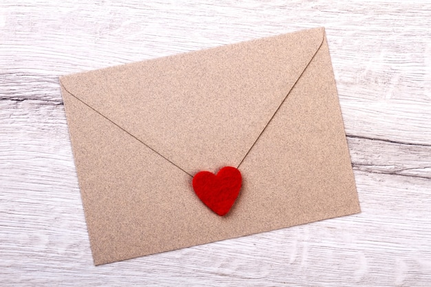Сердце ткани на конверте. письмо на деревянной поверхности. отправить любовное письмо возлюбленной. сообщение сочувствия на бумаге.