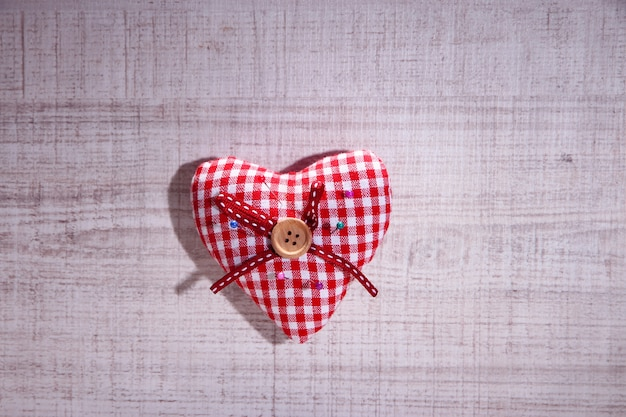 Fabric heart with color  pins on wooden