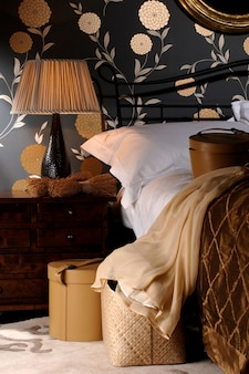 Fabric lampshade on the lamp at the big bed with pillows in the bedroom
