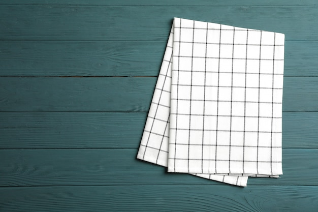 Fabric napkin on wooden background, space for text