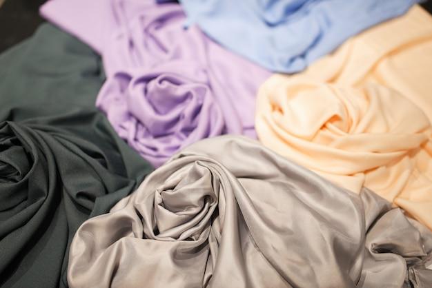 Ткань на столе крупным планом, швейная мастерская или текстильный магазин, никто. выбор красочной ткани в магазине