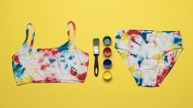 Краски для ткани и комплект нижнего белья в стиле «галстук-краситель» на желтой поверхности. цветное белье в домашних условиях.