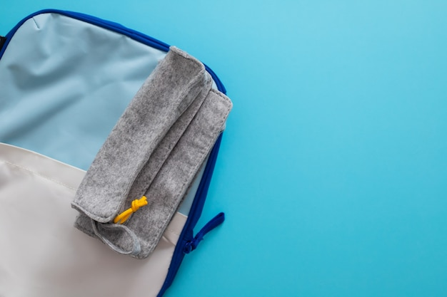 Fabric pencil case and  backpack on blue background