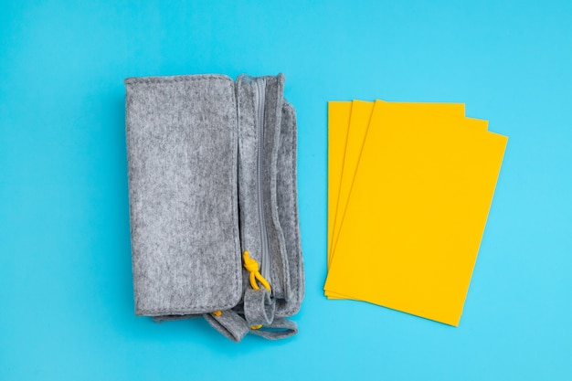 青い背景にファブリックのペンケースと黄色の封筒
