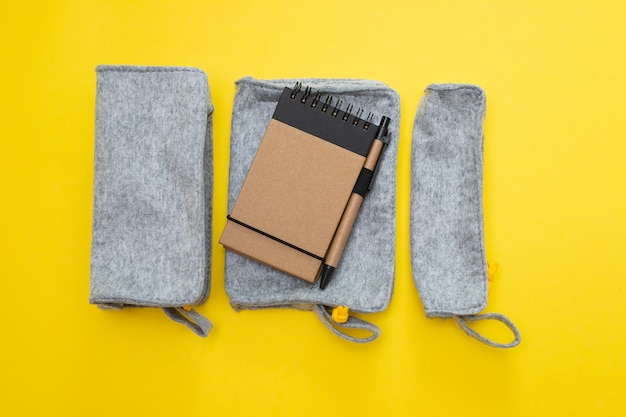 Fabric pencil cases with notepad on yellow background