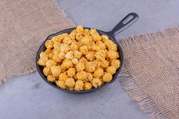 Кусочки ткани под сковородой, наполненной попкорном со вкусом карамели, на мраморном фоне. фото высокого качества
