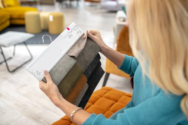 生地サンプル。正しい色を選択して、女性の細い手で布張りの家具に使用するさまざまな色の生地のサンプル。