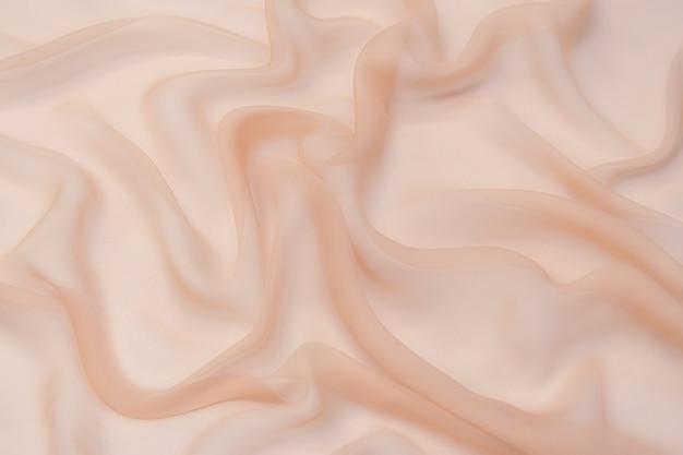 Текстура ткани, фон для дизайна. текстура бежевого шелка или хлопчатобумажной или шерстяной ткани. красивый узор из волнистой ткани.