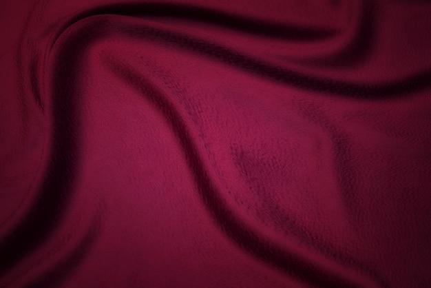 生地の質感、デザインの背景。赤い絹または綿またはウール生地の質感。波打った生地の美しいパターン。