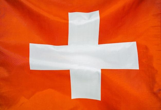 スイスの生地の質感の旗。風に手を振るスイスの旗